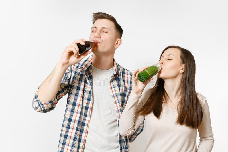 Young pretty couple man and woman drinking green detox smoothies, cola in glass bottle isolated on white background. Young pretty couple men and women drinking royalty free stock photography