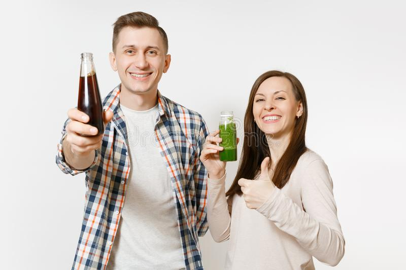 Young pretty couple man and woman holding green detox smoothies, cola in glass bottle isolated on white background. Young pretty couple men and women holding stock image