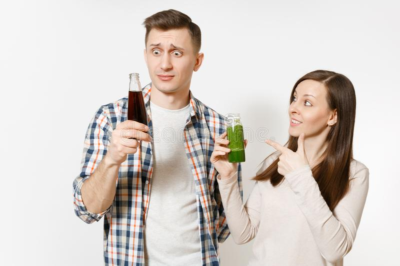 Young pretty couple man and woman holding green detox smoothies, cola in glass bottle isolated on white background. Young pretty couple men and women holding stock photography