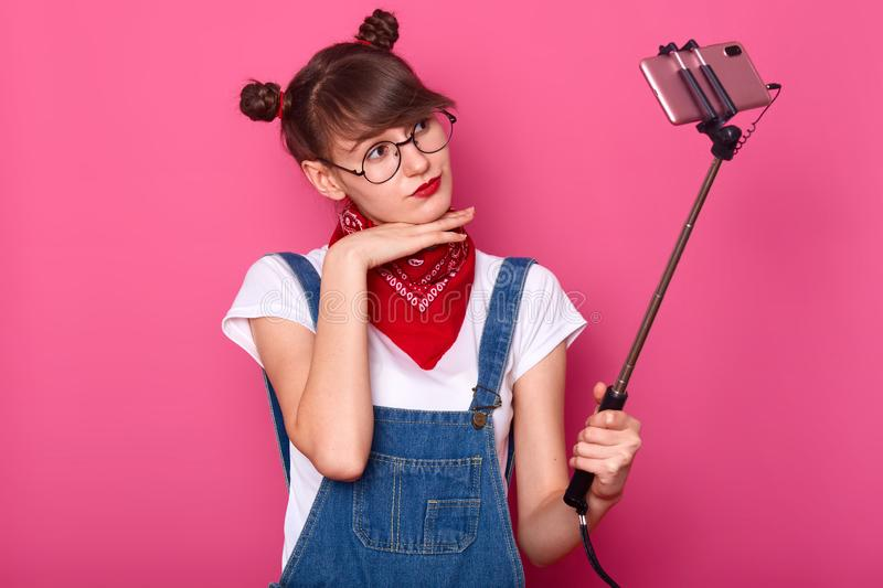 Young pretty dark haired women taking selfie on cell phone, using selfie stick, keeps hands under chin, dressed denim overalls and royalty free stock photography