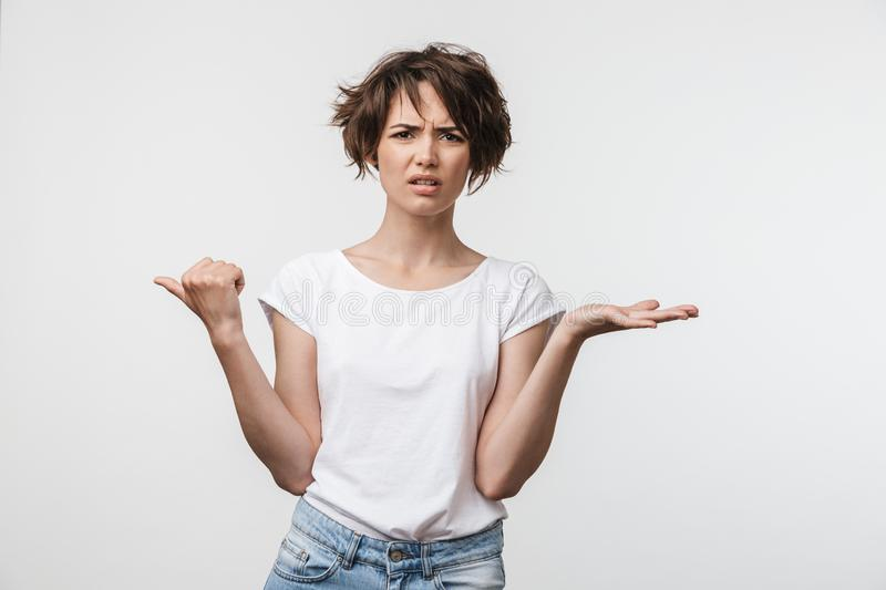 Young pretty displeased shocked woman posing isolated over white wall background pointing to copyspace royalty free stock images
