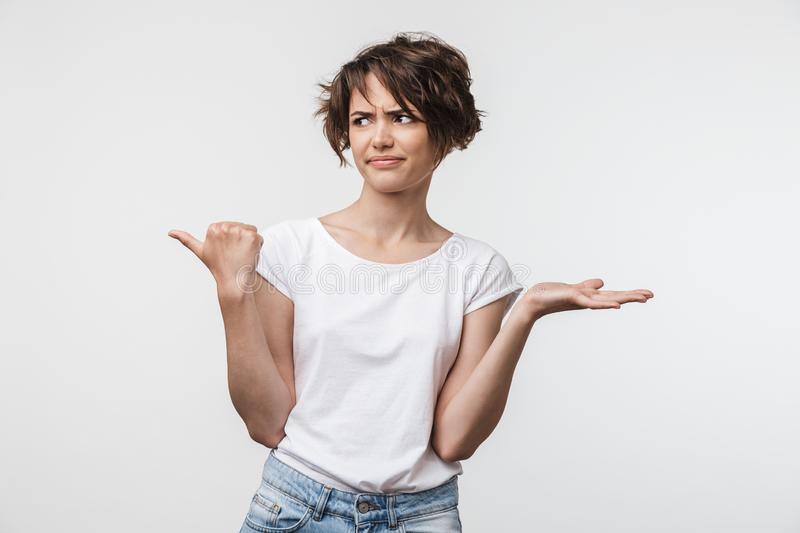 Young pretty displeased shocked woman posing isolated over white wall background pointing to copyspace royalty free stock photos