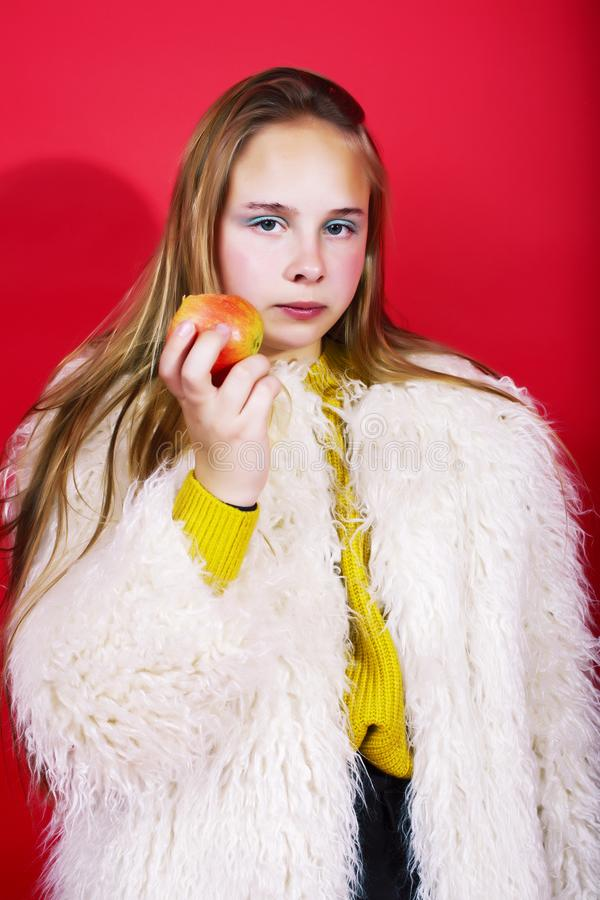 Young pretty emitonal posing teenage girl on bright red background eating apple, happy smiling lifestyle people concept stock photo