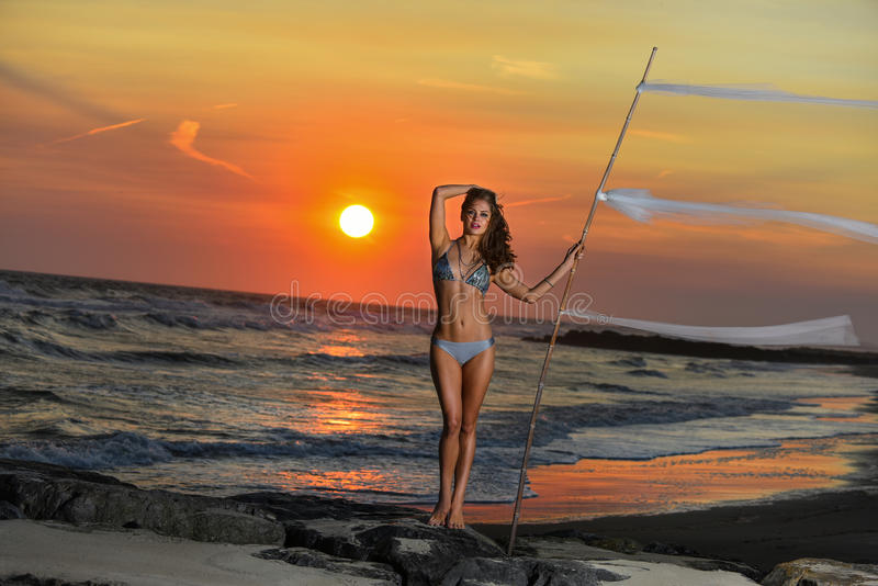 Young pretty fashion sporty woman in bikini posing outdoor on the beach. royalty free stock photo