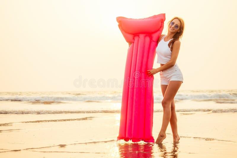 Young pretty fashion woman body posing in summer with mattress in black bikini and having fun royalty free stock photo
