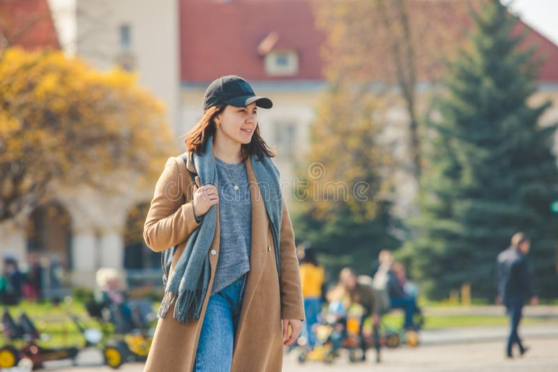 Young pretty fashionable woman walking in brown coat by street stock photography