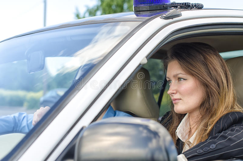 Young pretty female agent. Driving the car stock image