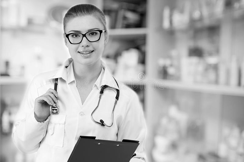 Young pretty female doctor in white uniform on blurry medicine b stock image