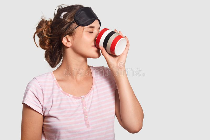 Young pretty female wakes up in morning, wears sleep mask and pyjamas, drinks hot coffee, tries to feel brave, isolated over white royalty free stock photography