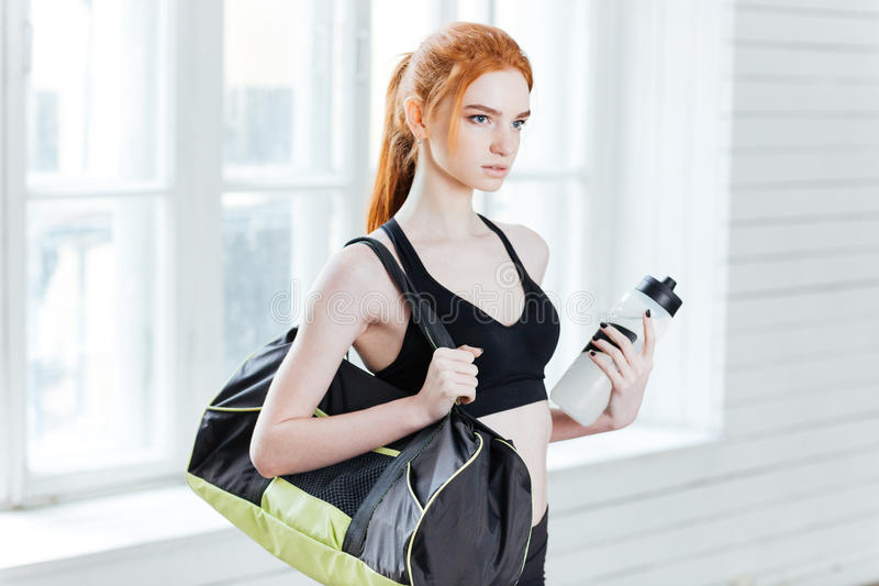 Young pretty fitness woman with sports bag and water bottle stock photos