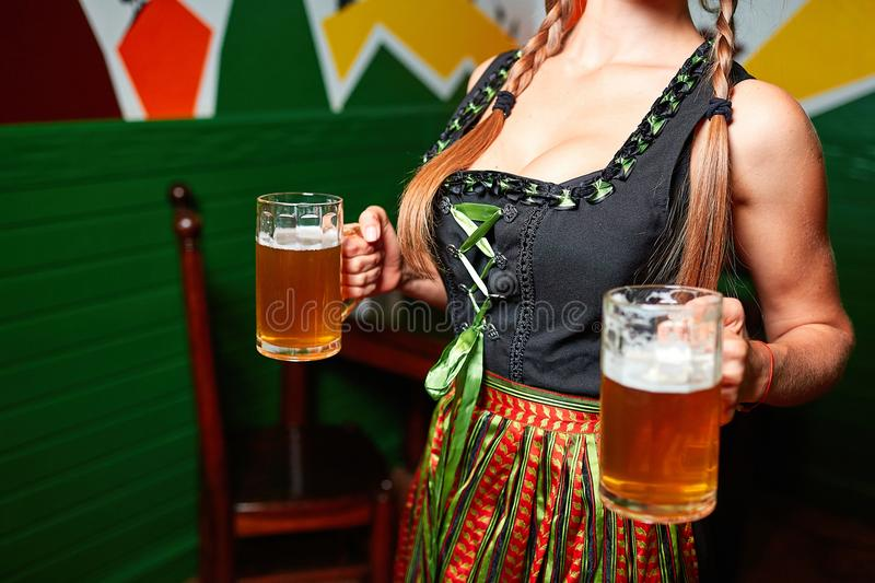 Young pretty girl in the bar with glass of beer. Beautiful waitress in traditional german costume holding beer glass in the bar royalty free stock photo