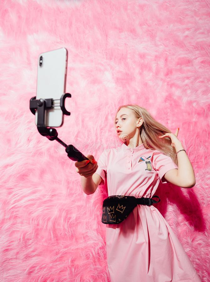 Young pretty girl blogger dressed in fashion pink dress make a selfie on the background of pink fur wall in the show royalty free stock image