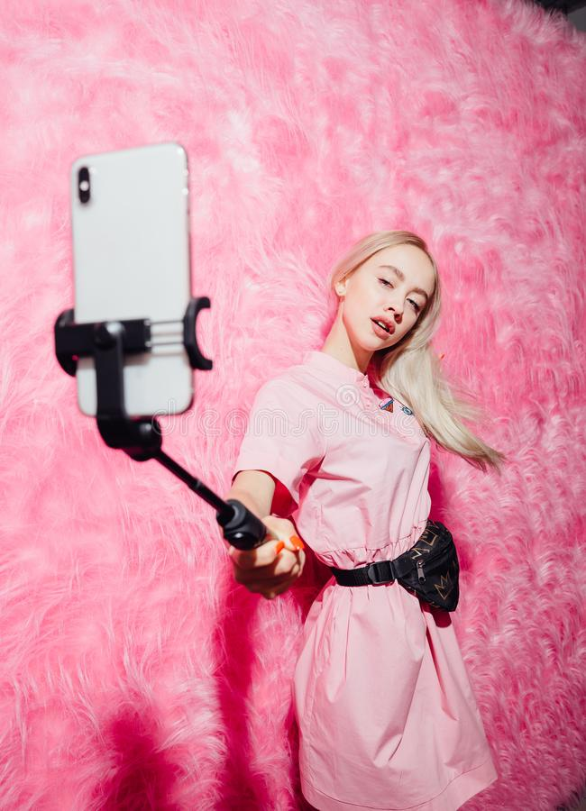 Young pretty girl blogger dressed in fashion pink dress make a selfie on the background of pink fur wall in the show royalty free stock photography