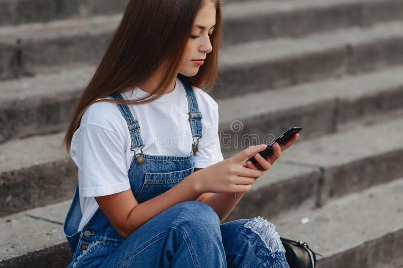 Young pretty girl with briefcase sitting on stairs and writing s royalty free stock photo