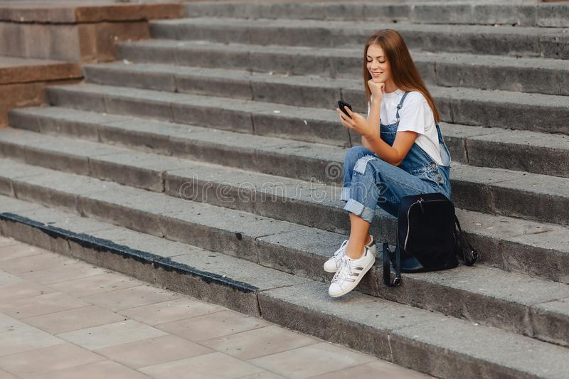 Young pretty girl with briefcase sitting on stairs and writing s royalty free stock image