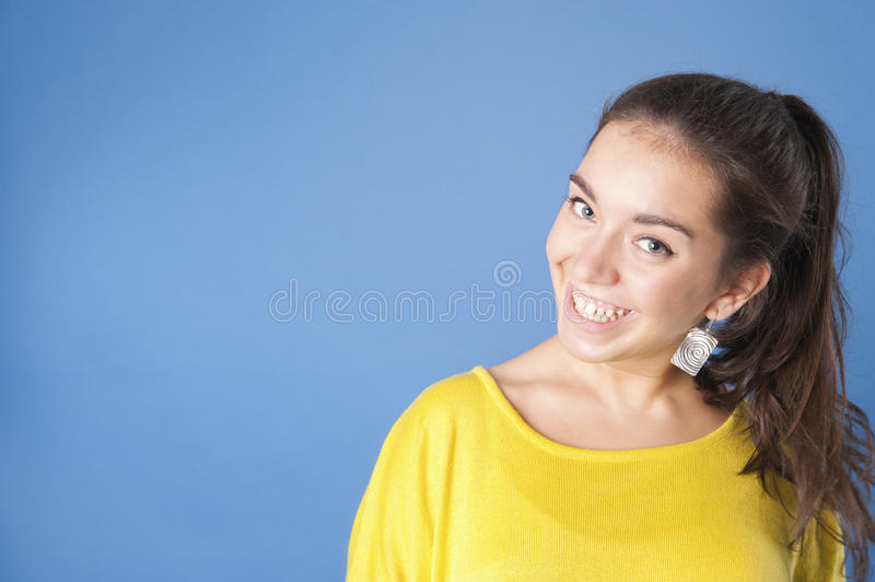 Young pretty girl in a bright yellow sweater on a blue background.. royalty free stock images