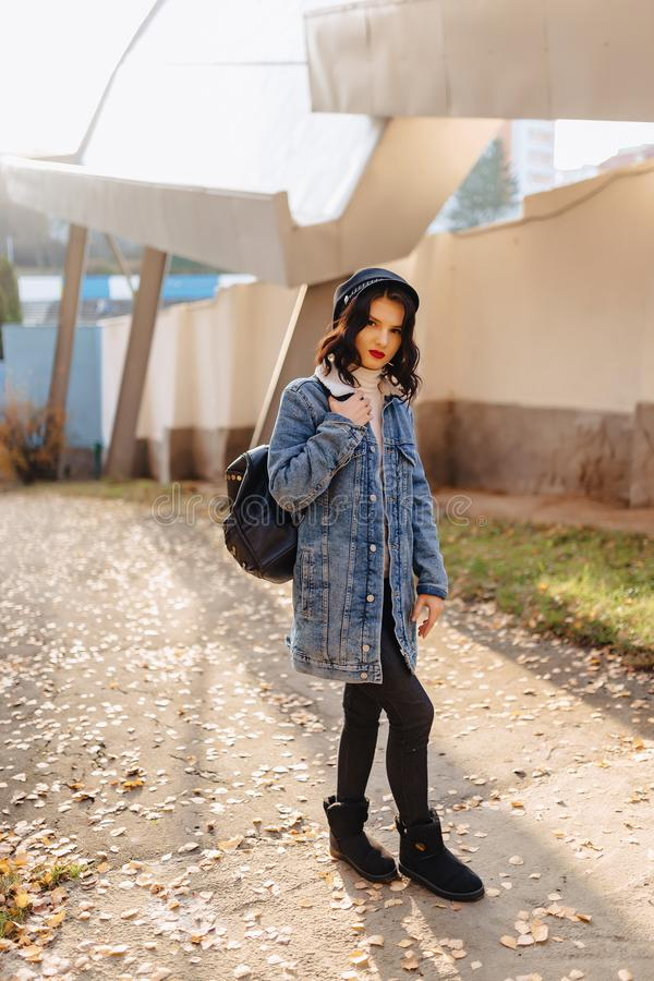Young pretty girl in a denim coat walks in the autumn city royalty free stock photo