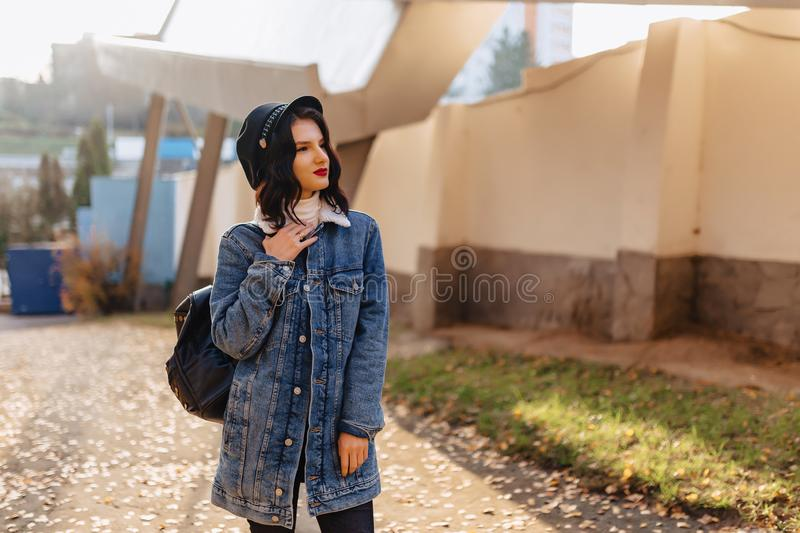 Young pretty girl in a denim coat walks in the autumn city stock images