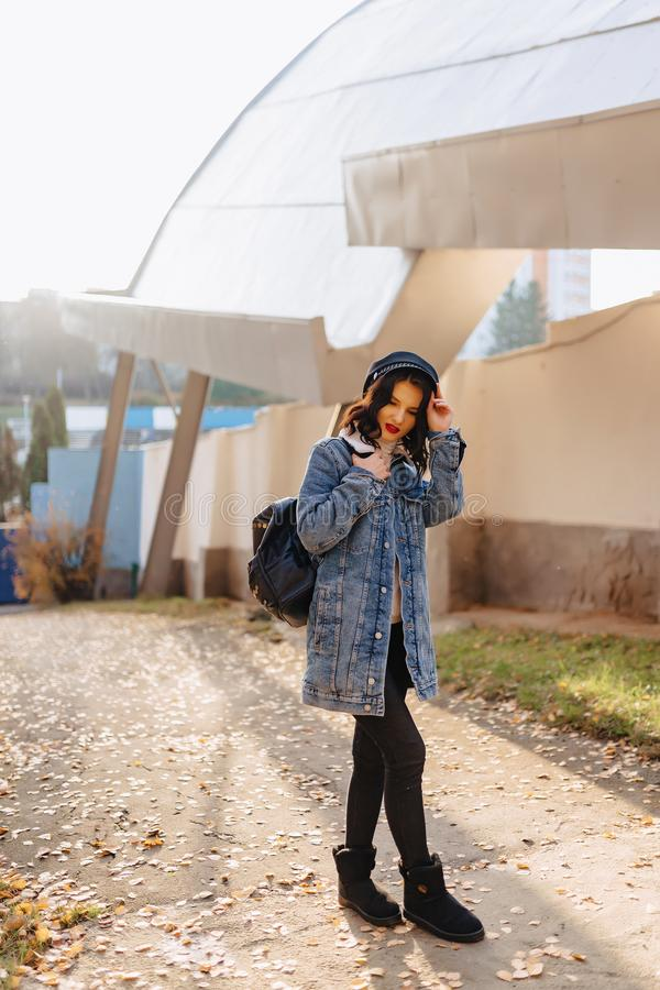 Young pretty girl in a denim coat walks in the autumn city royalty free stock photography