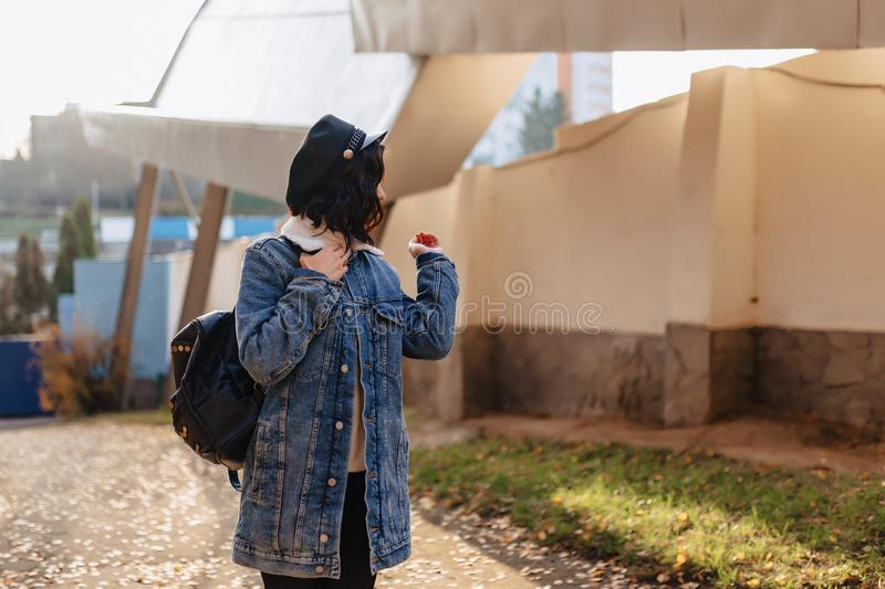 Young pretty girl in a denim coat walks in the autumn city stock photography