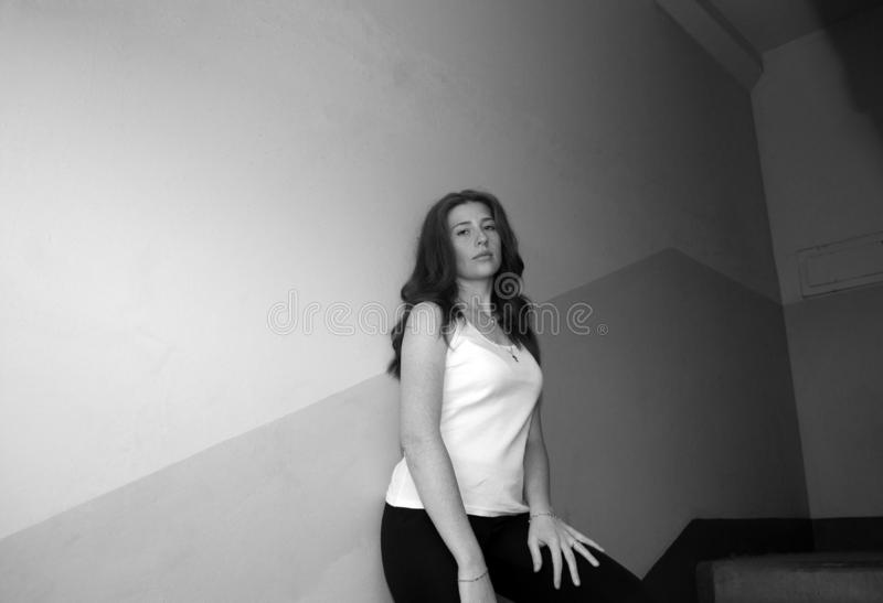 A young pretty girl with loose hair in a t-shirt and trousers stands in the entrance of the house on the landing. Black and white photo stock images