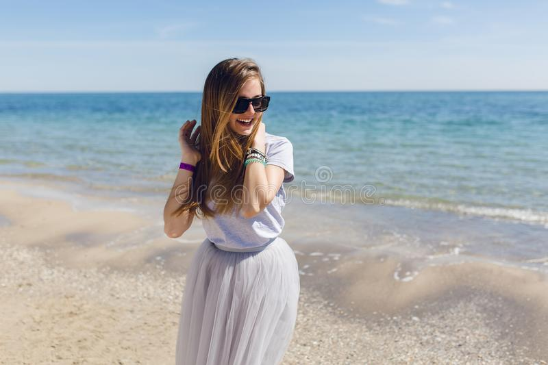 Young pretty girl in lush gray skirt and T-shirt is standing near sea. She has long hair and looks very happy.  stock images