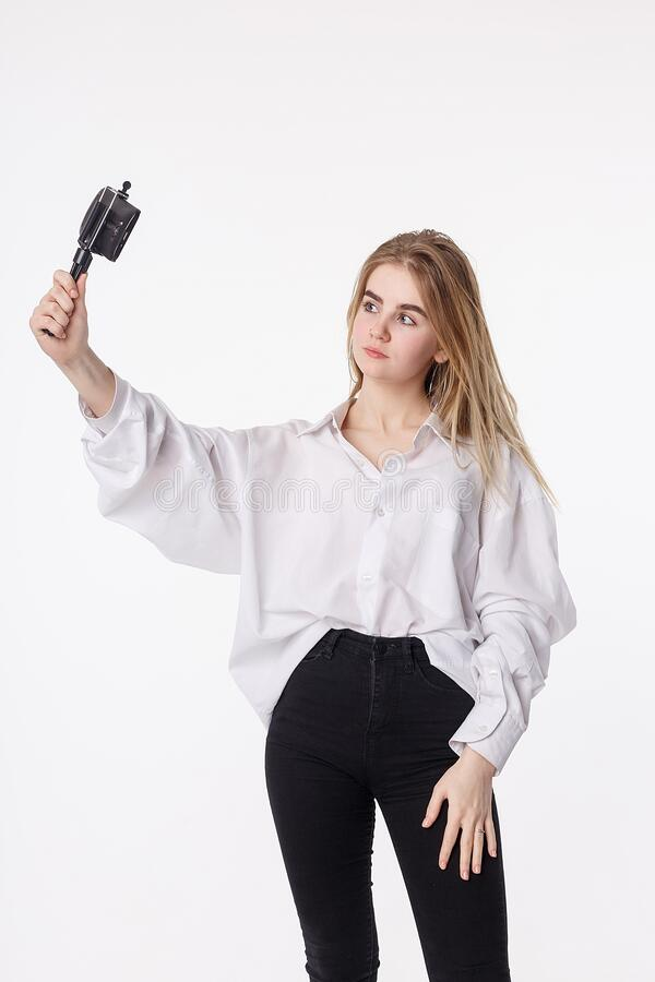 Young pretty girl making self portrait with smartphone attached to small tripod stock photos