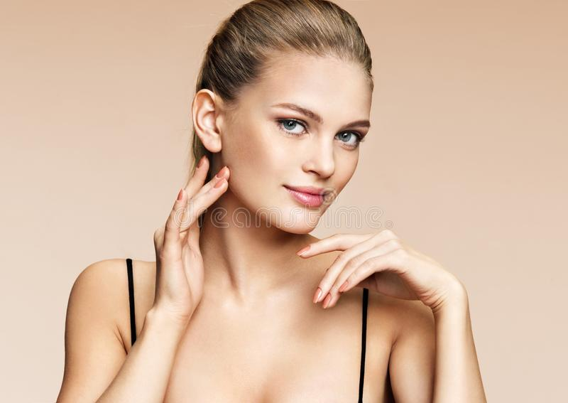 Young pretty girl with natural makeup on beige background. royalty free stock image