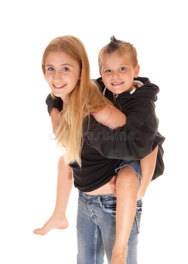 Young pretty girl is piggybacking little brother. stock photos