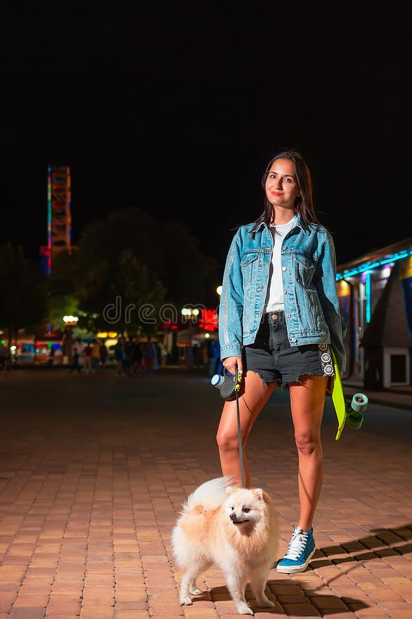 A young pretty girl posing with a skateboard in her hands and a German Spitz dog breed. There`s an amusement Park in the stock photos