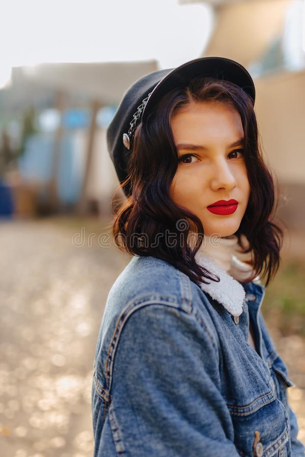 Young pretty girl with red lips and short hair in a denim coat walks in the autumn city stock images