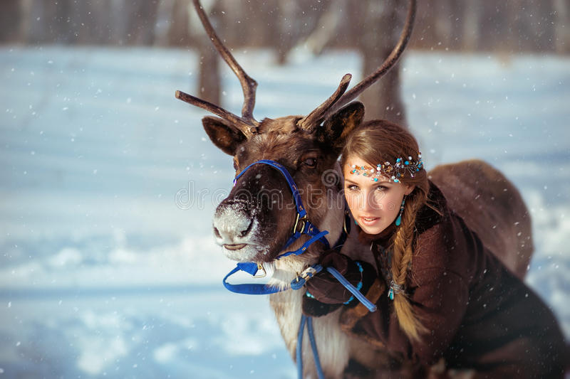 Young pretty girl with a reindeer in the winter royalty free stock photography
