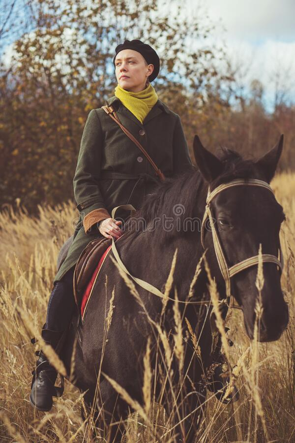 Young pretty girl riding a horse wearing a retro coat stock photo