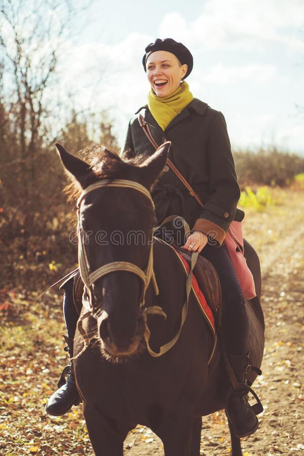 Young pretty girl riding a horse wearing a retro coat royalty free stock images