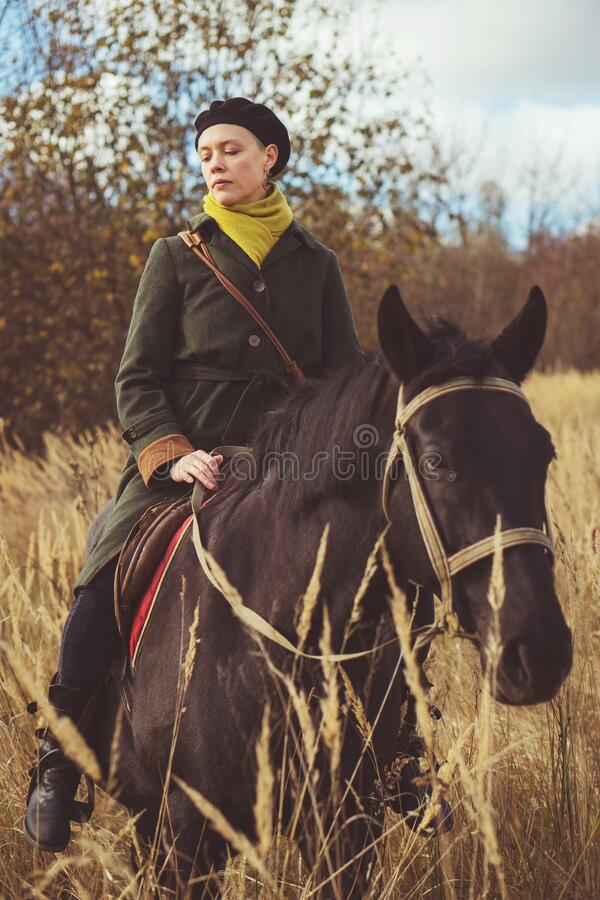 Young pretty girl riding a horse wearing a retro coat royalty free stock photography