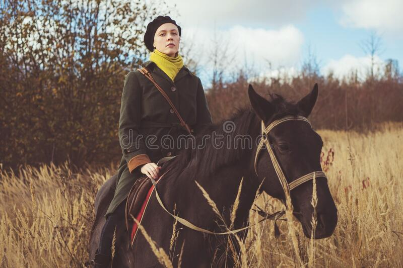 Young pretty girl riding a horse wearing a retro coat royalty free stock photo