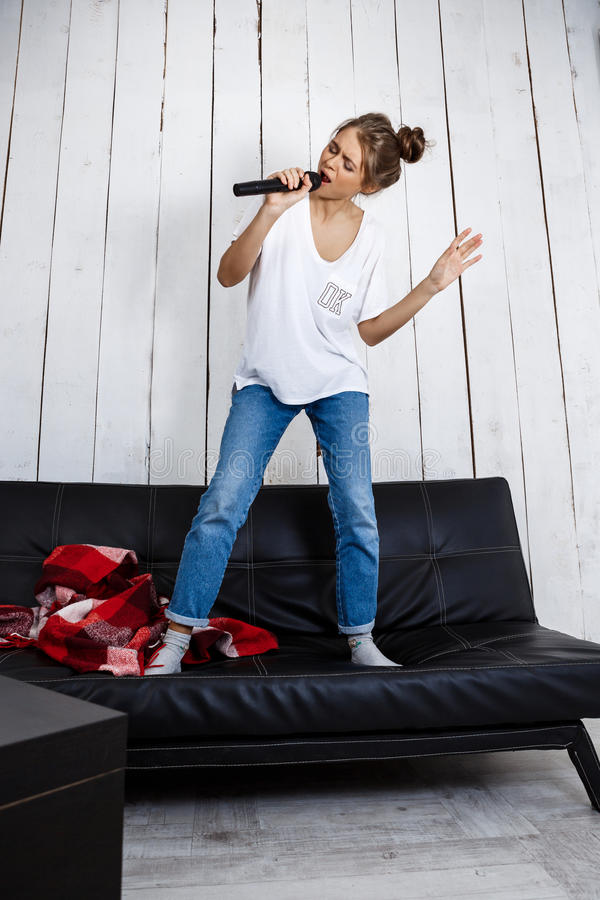 Young pretty girl singing in microphone on sofa at home. royalty free stock photo