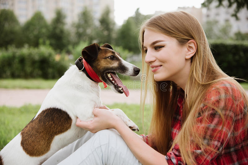 Young pretty girl sit at the lawn with dog. stock photo