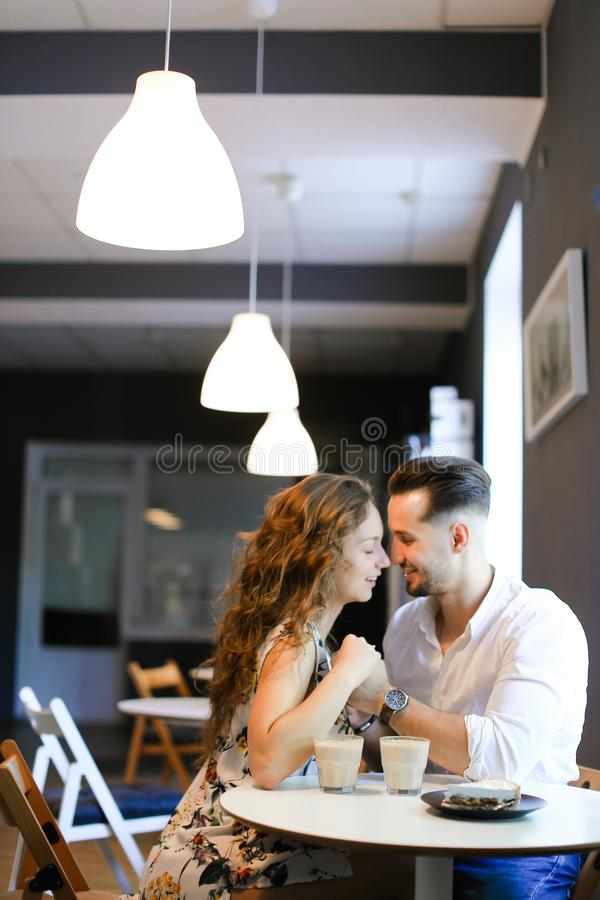 Young pretty girl sitting with boyfriend at cafe and resting. royalty free stock photo