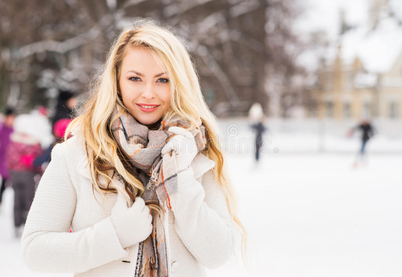 Young and pretty girl skating on outdoor ice-rink royalty free stock image
