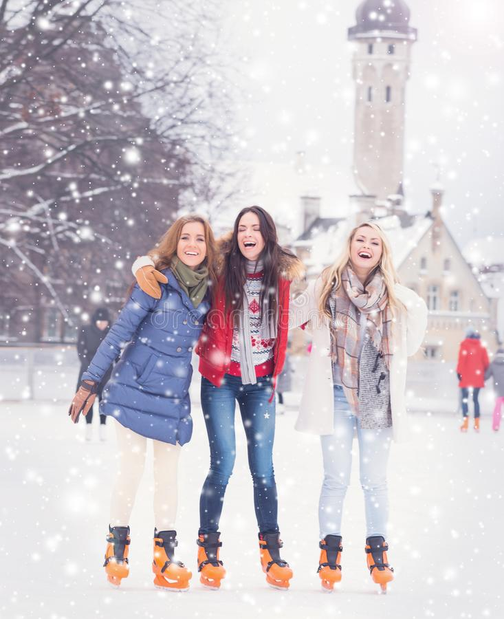 Young and pretty girl skating on outdoor open air ice-rink at wi. Beautiful skating girls. Open air rink at winter. Falling snow. Christmas concept royalty free stock photography