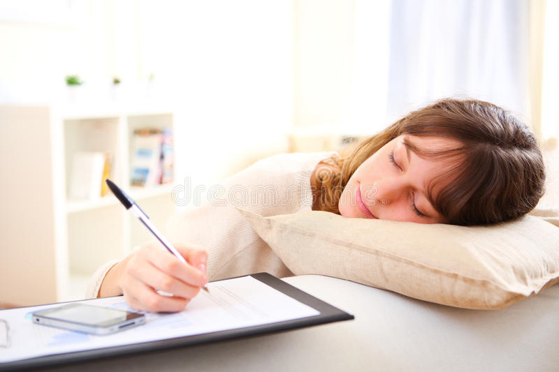 Young pretty girl sleeping while working home royalty free stock photography