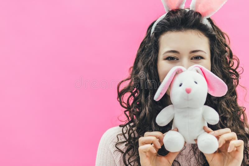 Young pretty girl standing on a pink background. On the head of the ears of the bunny. During this, he holds a soft stock images