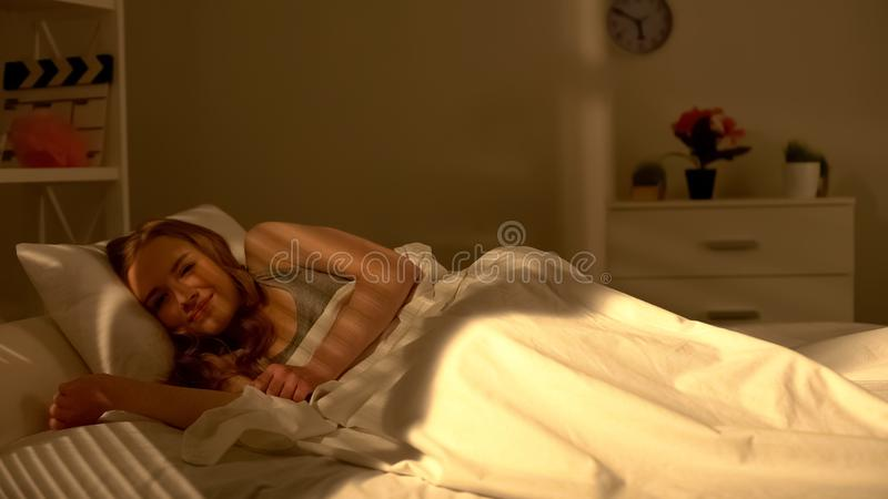 Young pretty girl waking up in bed and smiling, good mood in morning, positive. Stock photo royalty free stock photo