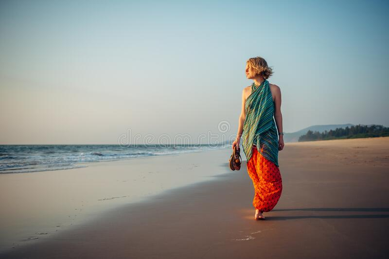Young pretty girl walking along the seashore and admires the sunset. Blonde in bright clothes on sandy beach in the light of. Setting sun stock photo