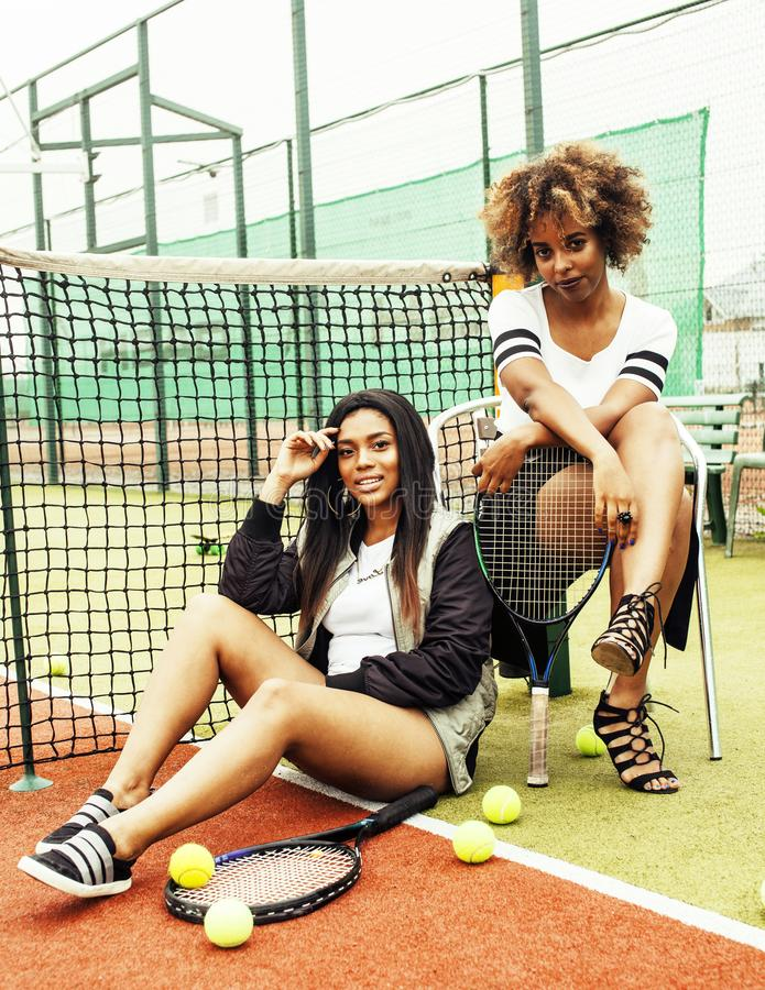 young pretty girlfriends hanging on tennis court, fashion stylis royalty free stock photo