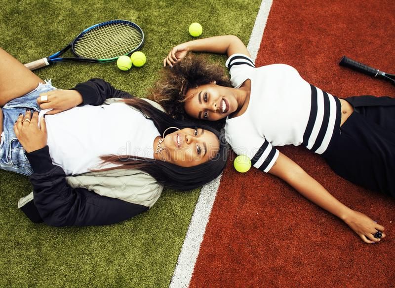 young pretty girlfriends hanging on tennis court, fashion stylis stock photos