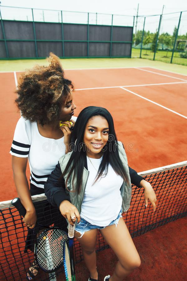 Young pretty girlfriends hanging on tennis court, fashion stylish dressed swag, best friends happy smiling together royalty free stock photography