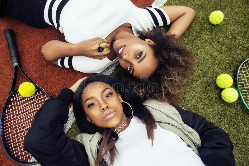 Young pretty girlfriends hanging on tennis court, fashion stylish dressed swag, best friends happy smiling together royalty free stock photos