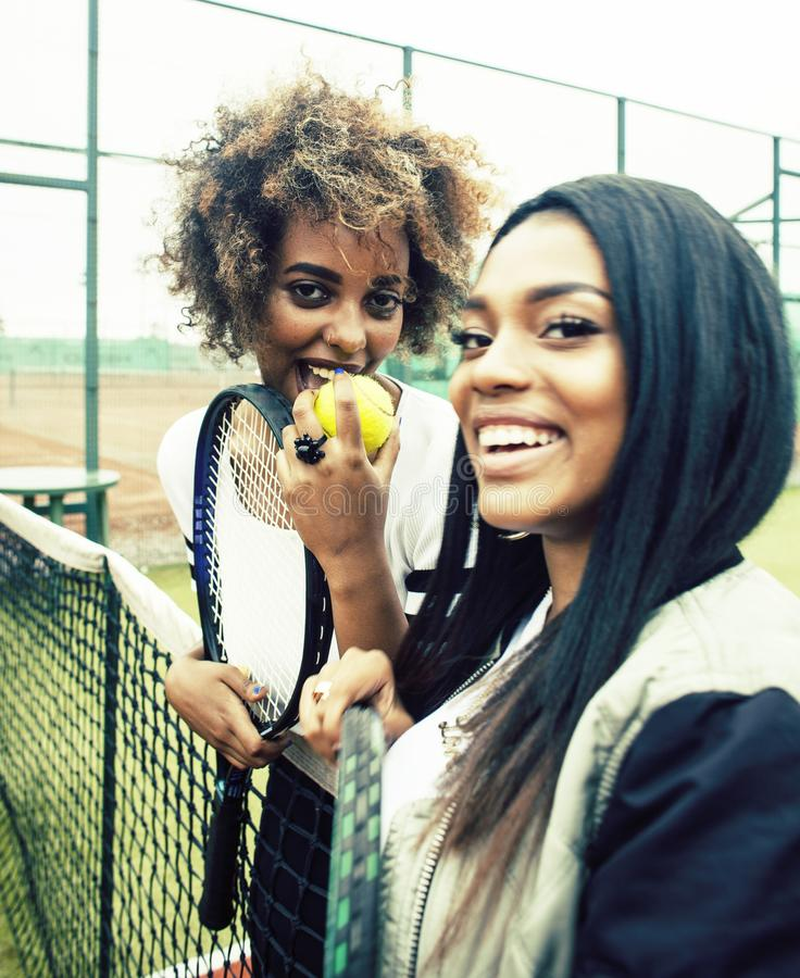 Young pretty girlfriends hanging on tennis court, fashion stylish dressed swag, best friends happy smiling together royalty free stock images